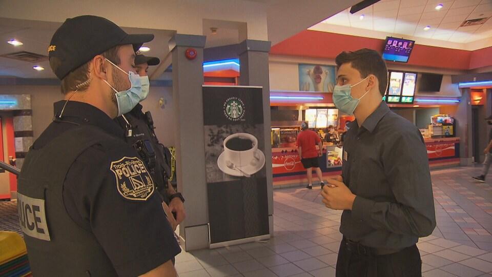 Deux policiers discutent avec un employé du Cinéma Fleur de Lys à Trois-Rivières.