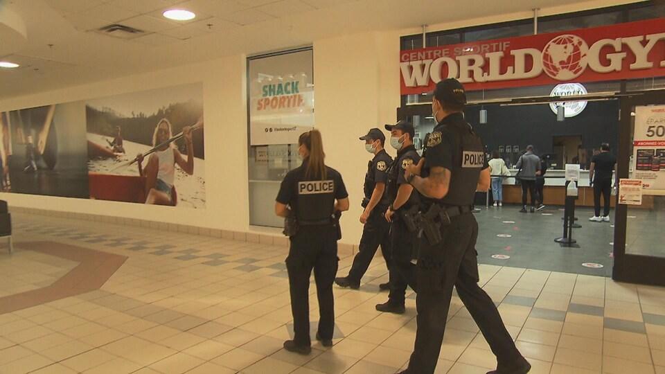 Quatre policiers sortent du Centre sportif World Gym.