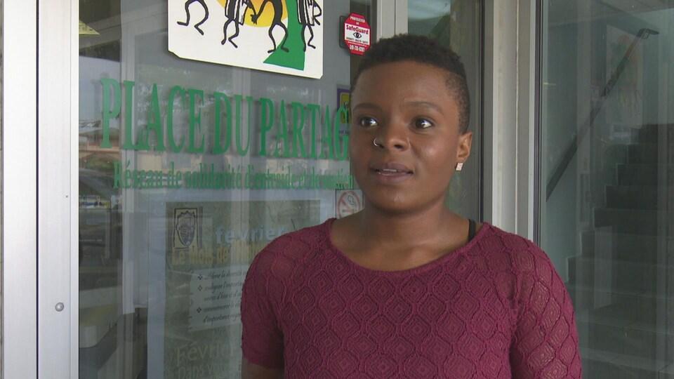 Une jeune femme dans un tricot pourpre parle à la caméra.