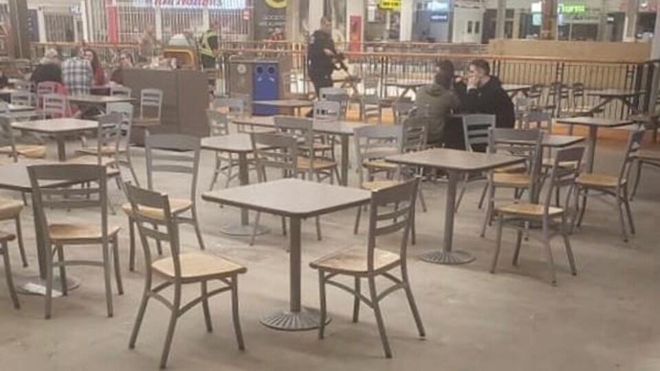 Un policier qui passe tout près de clients d'une aire de restauration au centre commercial Avalon.