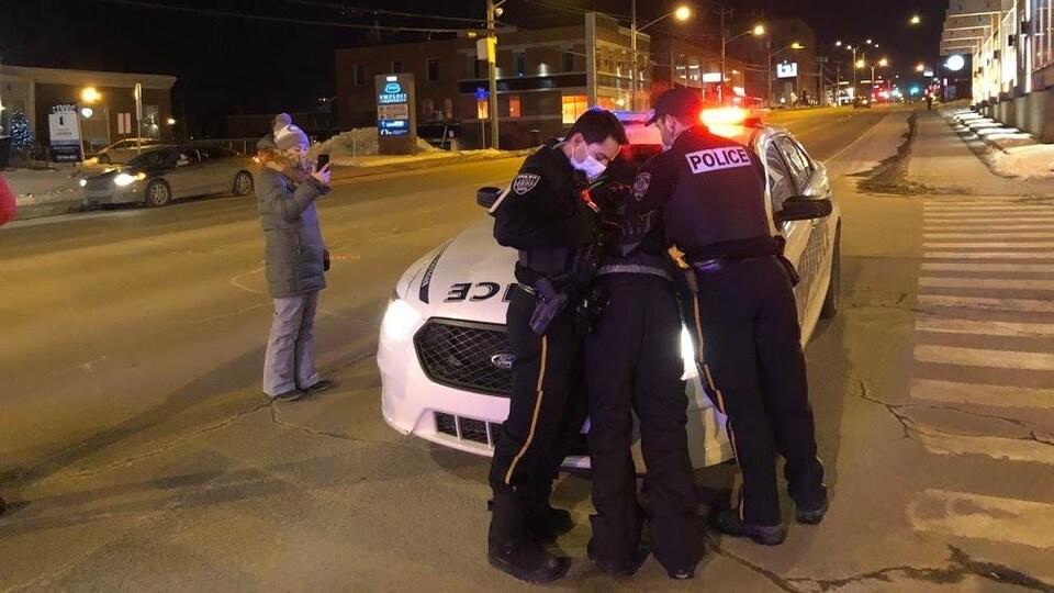 Les policiers maîtrisent un individu sur le véhicule de patrouille.
