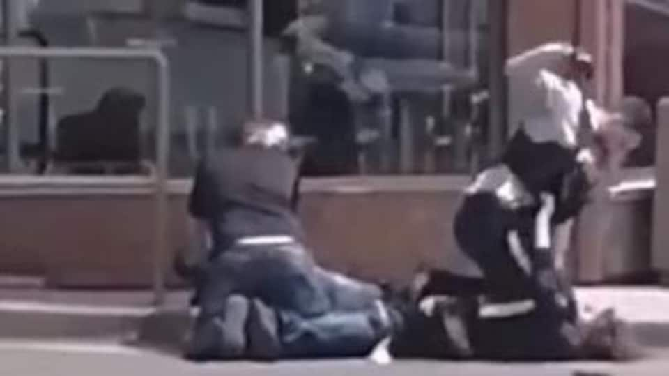 Un agent de la GRC semble frapper un homme plaqué au sol lors d'une arrestation.