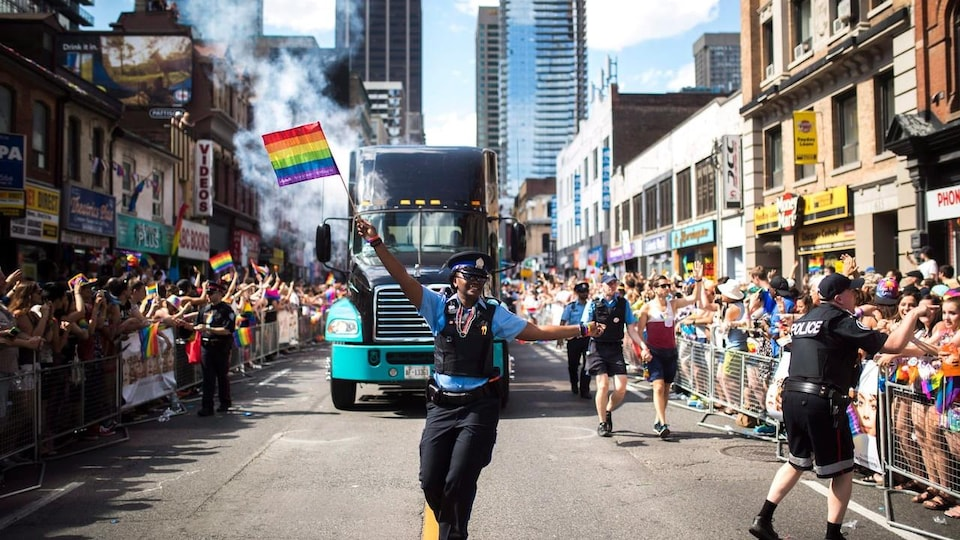 Une policière danse dans la rue en tenant un drapeau gai