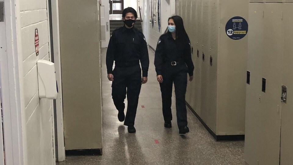 Deux apprentis policiers marchent dans un corridor.
