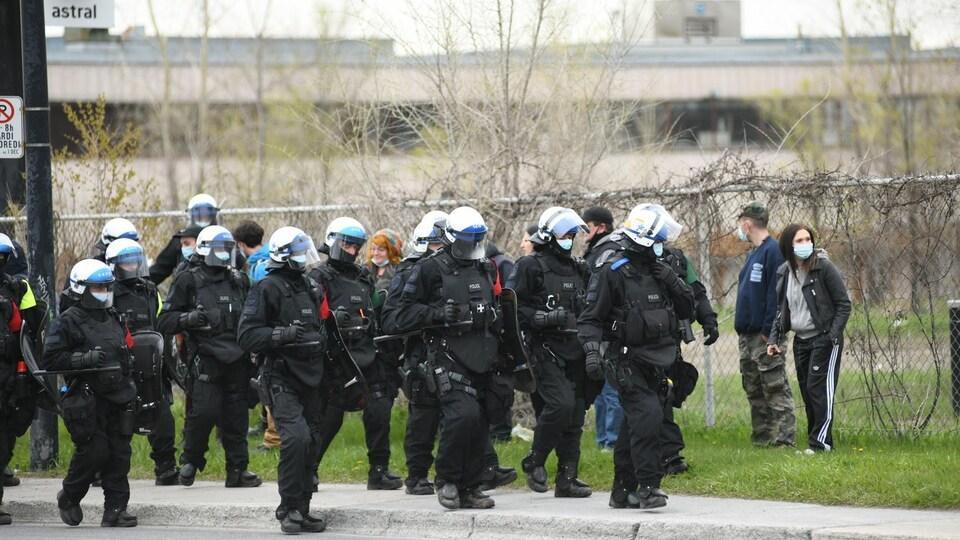 Des policiers casqués et munis de boucliers avancent sur le trottoir.
