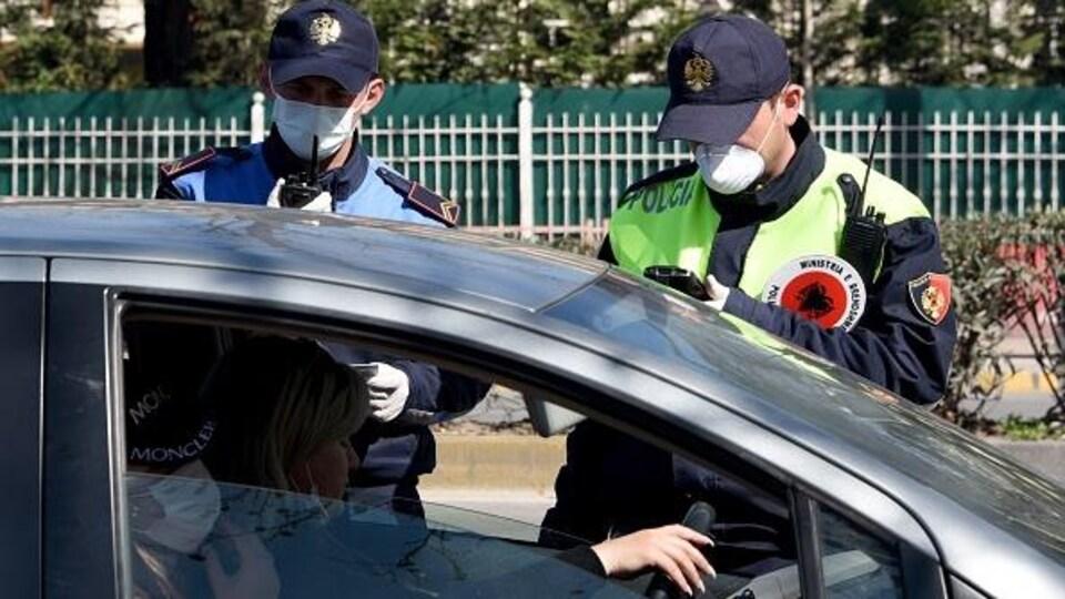 Un policier et un militaire portant des masques contrôlent une conductrice.