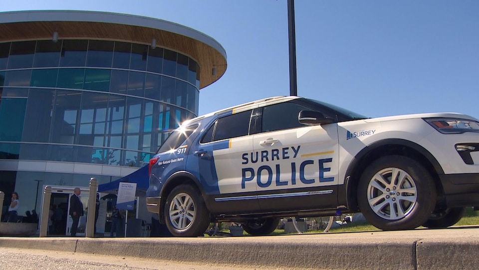 Une voiture de police de Surrey devant un édifice en verre.