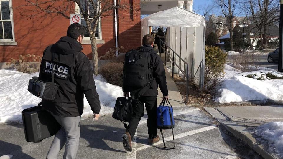 Des policiers entre à l'hôtel de ville.
