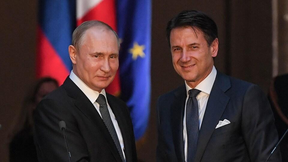 Les deux hommes sourient.