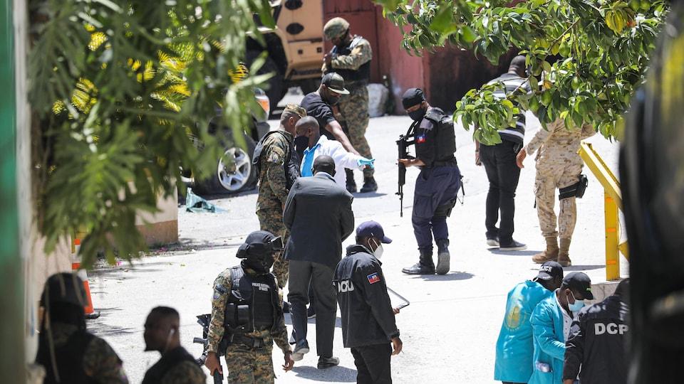 Des policiers, des scientifiques et des membres de l'armée cherchent des indices.