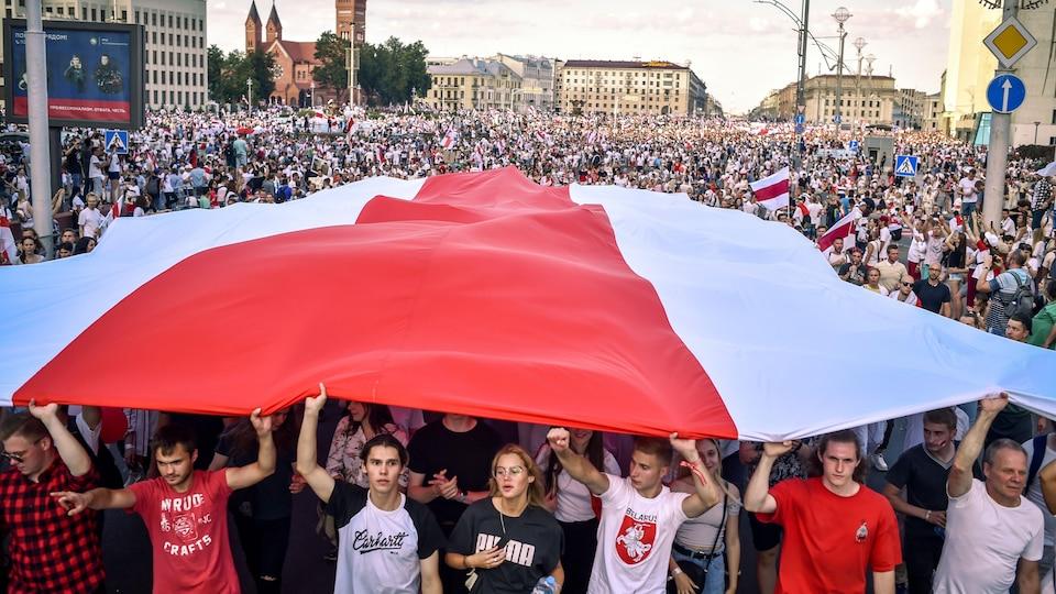 Une foule de manifestants sous un drapeau à Minsk.