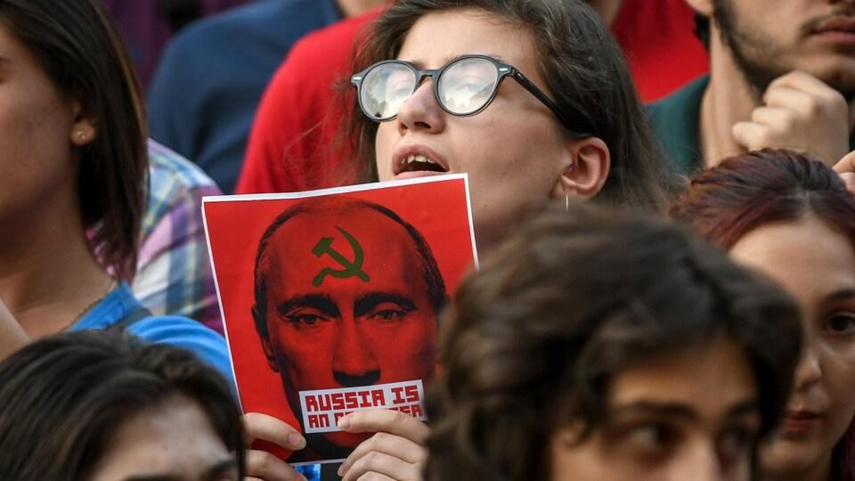 Parmi la foule, une jeune femme tient une pancarte rouge avec un slogan et le visage inquiétant de Vladimir Poutine.