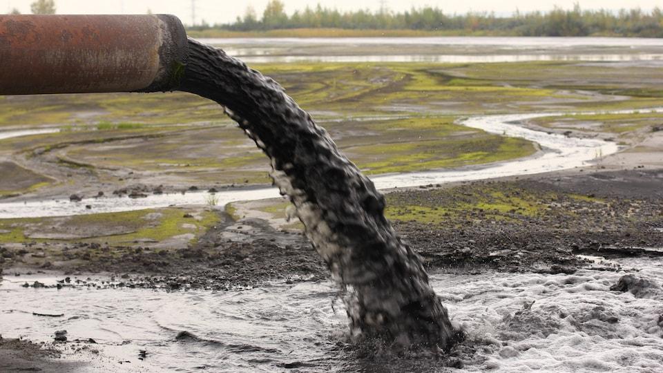 Un tuyau déverse de l'eau polluée sur un terrain vague.