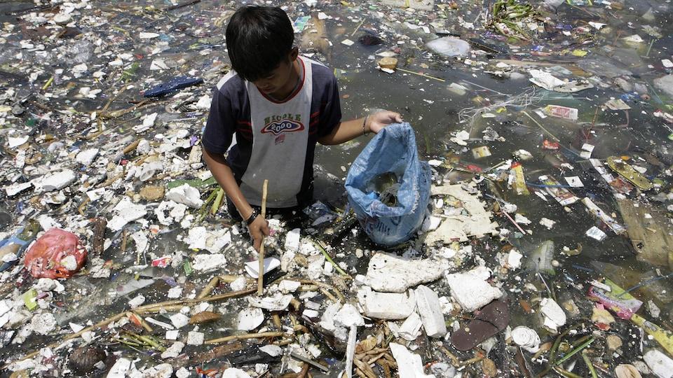 Un jeune tente de récupérer du plastique sur la côte de la ville de Manille. Il a de l'eau jusqu'à la taille et il est entouré d'une tonne de déchets qui flottent sur l'eau.