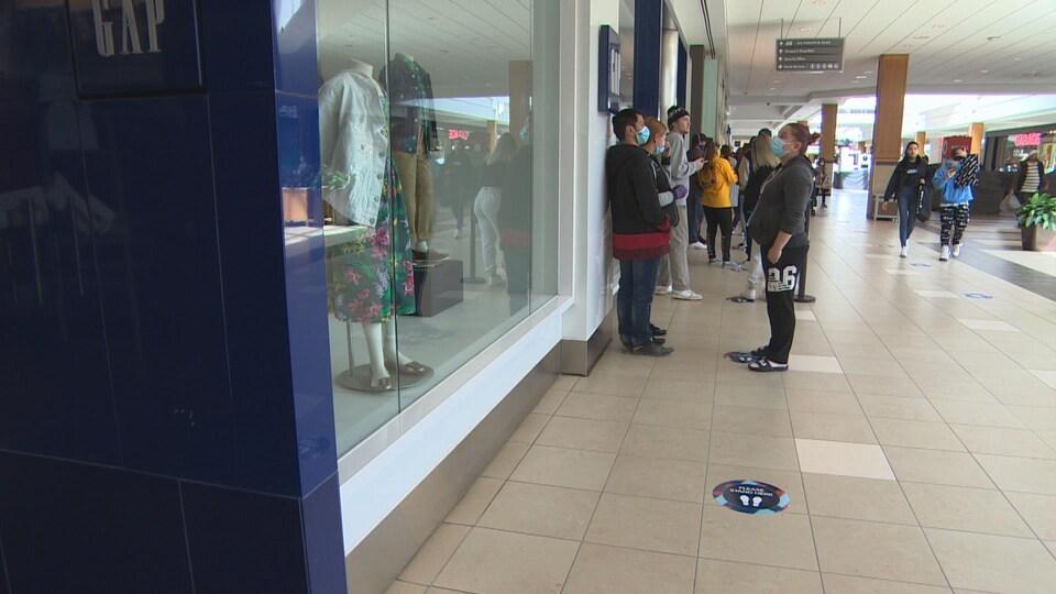 Dans le centre commercial, des clients font la file en respectant les marques au sol qui permettent des les distancier de façon appropriée. Certains portent de masques.