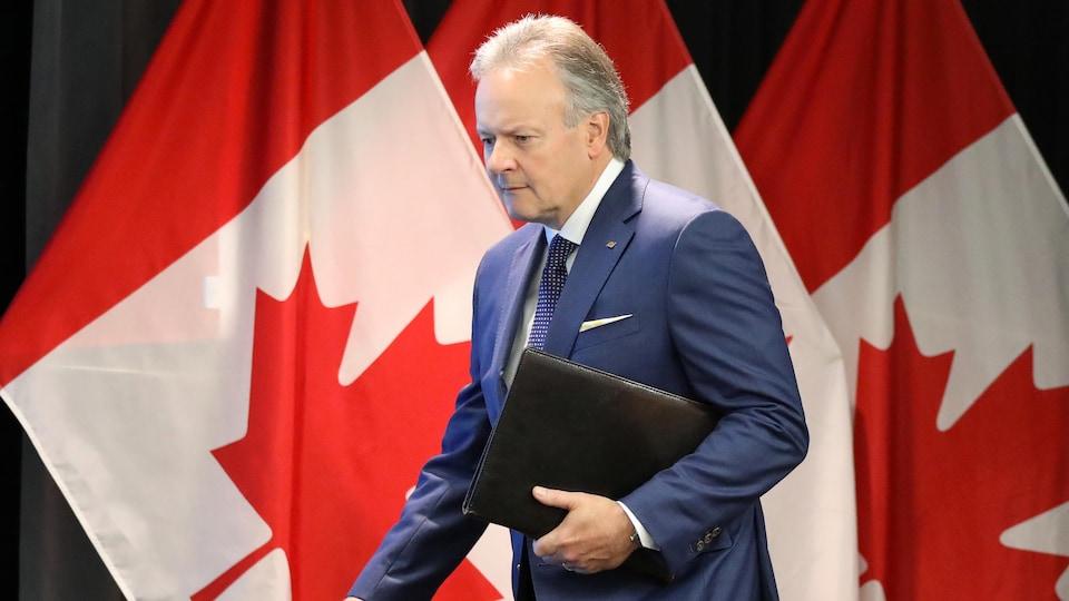 Le gouverneur de la Banque du Canada Stephen Poloz passe devant des drapeaux du Canada, juste avant de participer à une conférence de presse à Ottawa.