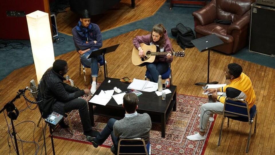 Cinq personnes assises en rond autour d'une table dans un studio prennent des notes.