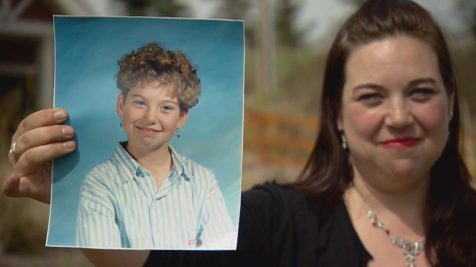 Une femme tient dans sa main droite une photo d'elle-même lorsqu'elle avait 10 ans.