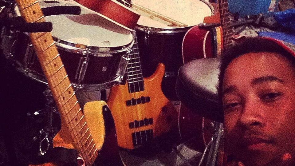Un homme montre ses guitares, ses percussions et d'autres instruments de musique.