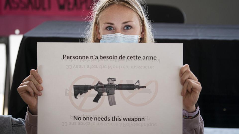Une étudiante tient une affiche sur laquelle on peut lire : Personne n'a besoin de cette arme.
