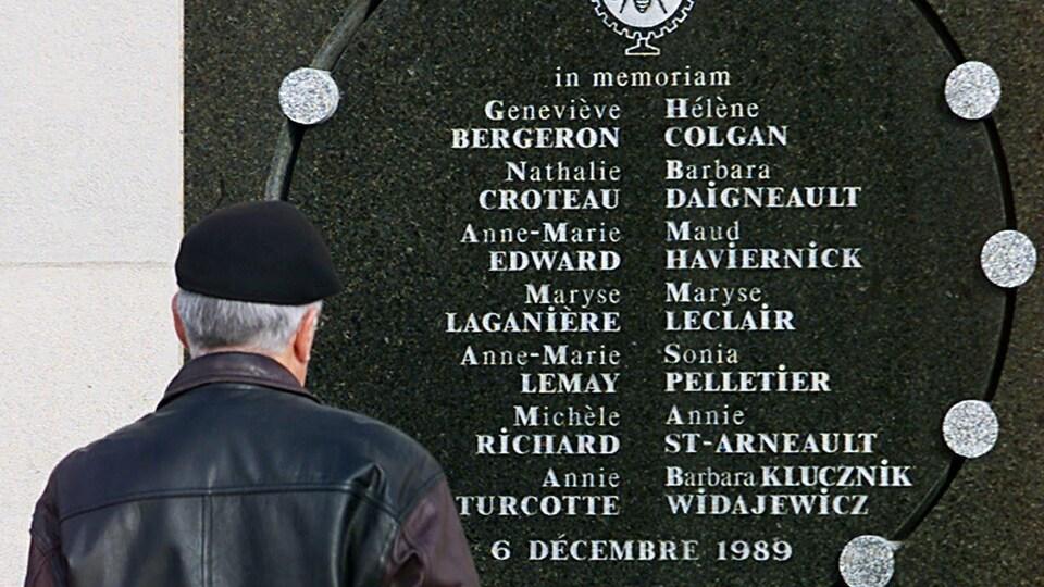 Un homme se tient debout devant la plaque commémorative sur laquelle sont inscrits les noms des 14 victimes.
