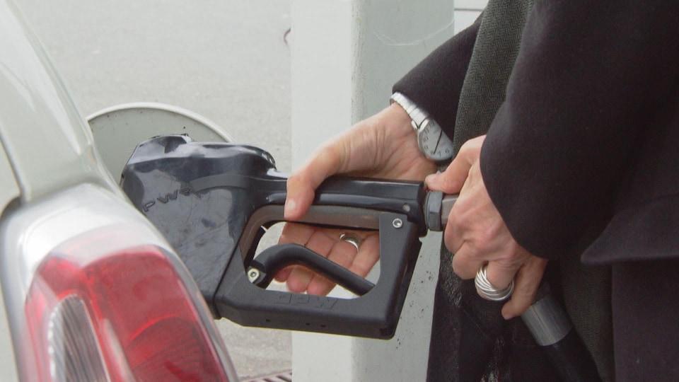 Une automobiliste debout à côté de sa voiture fait le plein d'essence en tenant la pompe dans ses mains.