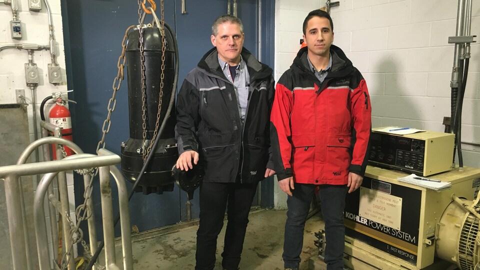 Deux hommes devant une pompe