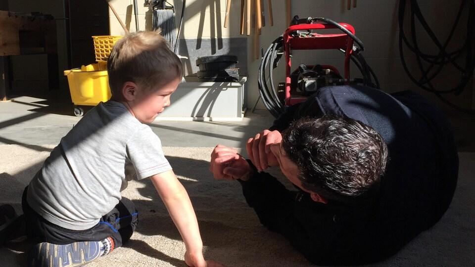 Un pompier allongé sur le côté, les mains vers son visage, échange un regard avec un enfant assis au sol.