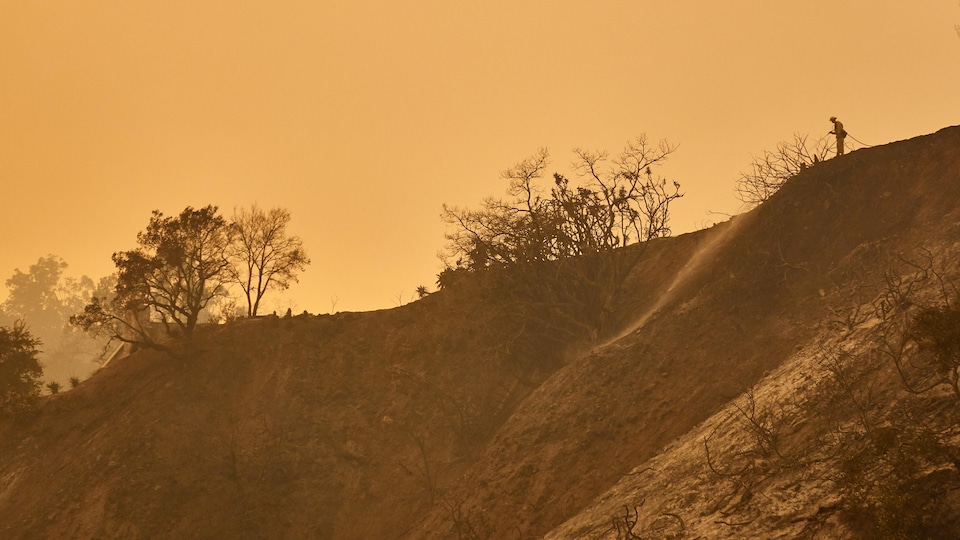 Un pompier termine de combattre un incendie dans les montagnes de Carpintiera, dans le nord-ouest de la Californie, le 12 décembre 2017.