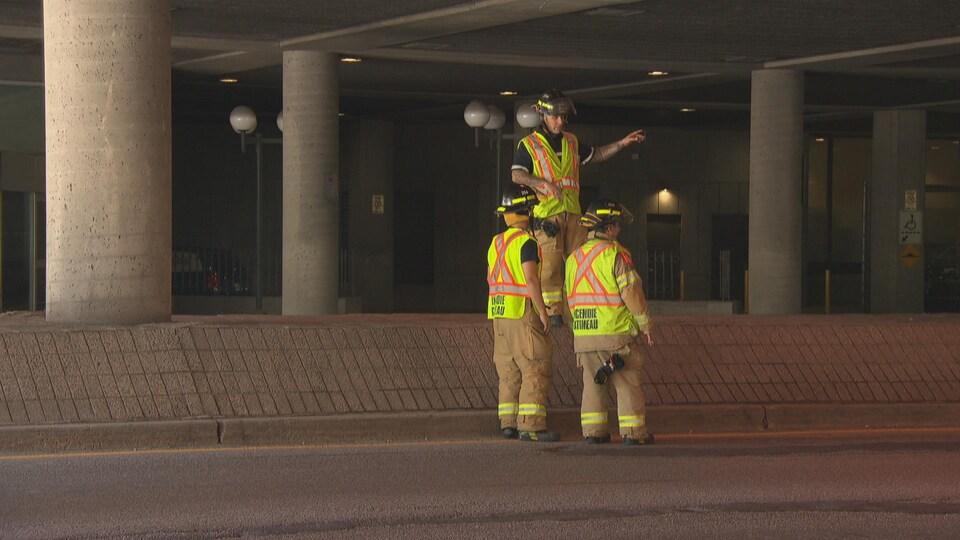 Des pompiers inspectent la structure qui surplombe le boulevard Maisonneuve dans le secteur Hull à Gatineau.