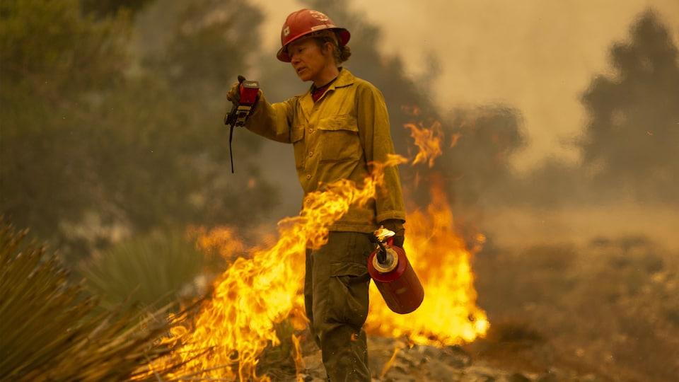 Une pompière se sert d'une torche pour combattre un feu.
