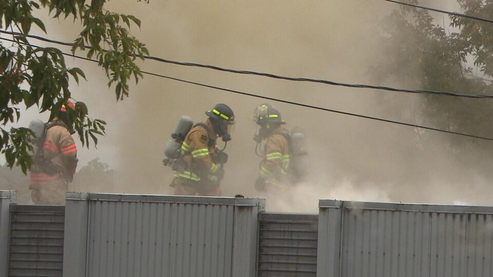 Des pompiers combattent un incendie sur le toit d'une résidence.