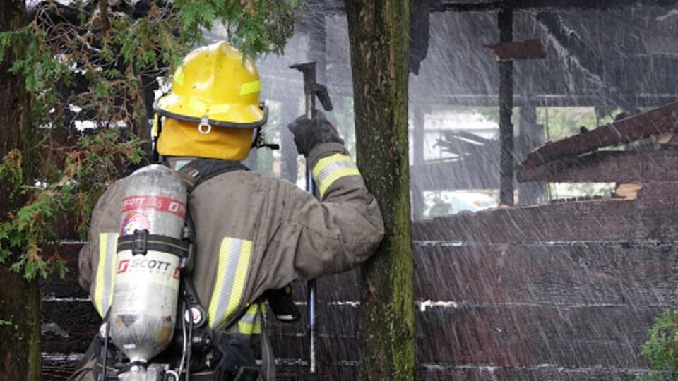 Un pompier tente d'éteindre un feu dans une remise.