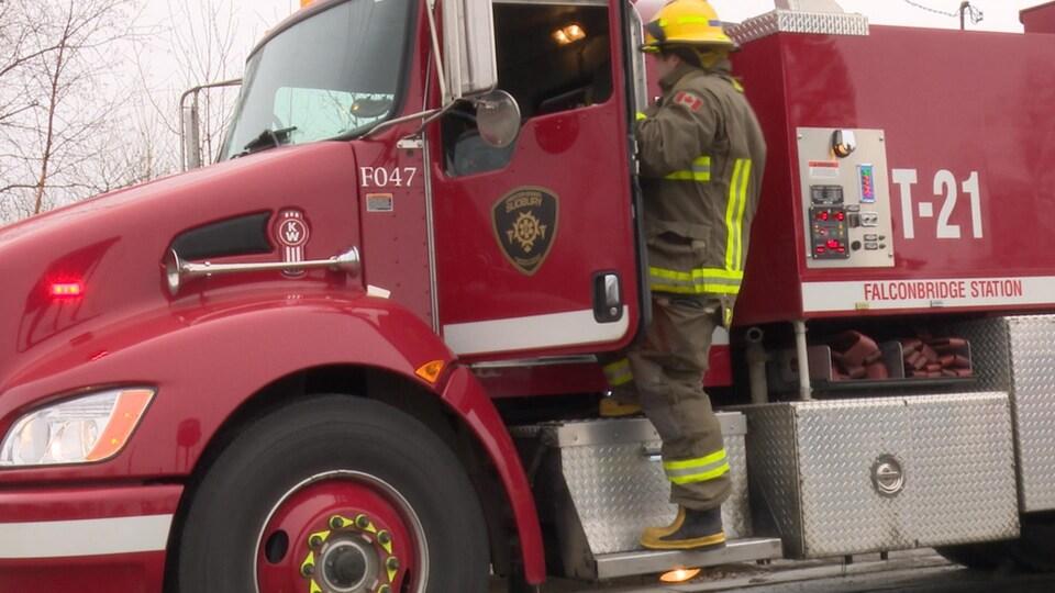 Un pompier monte dans son camion.
