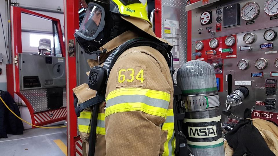Un pompier porte l'appareil respiratoire complet.