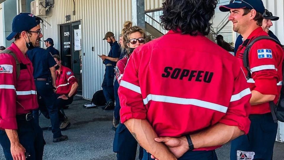 Des pompiers de la SOPFEU discutent ensemble et avec une collègue du service de lutte contre les incendies de la Colombie-Britannique.