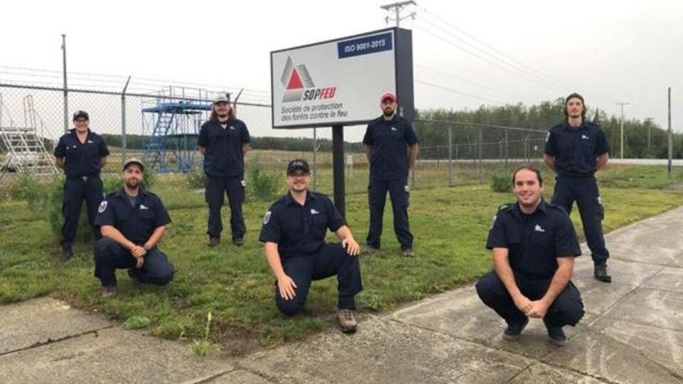 Sept pompiers posent chacun à deux mètres de distance devant une affiche de la SOPFEU.