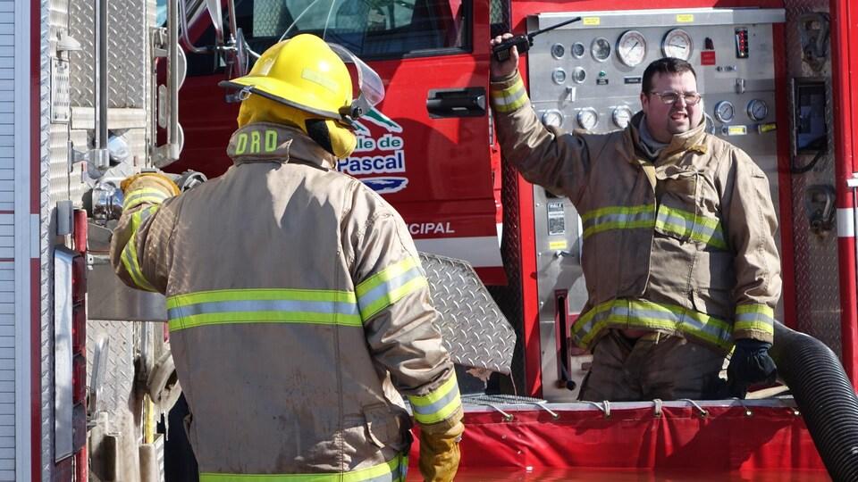 Des pompiers remplissent un bassin d'eau.