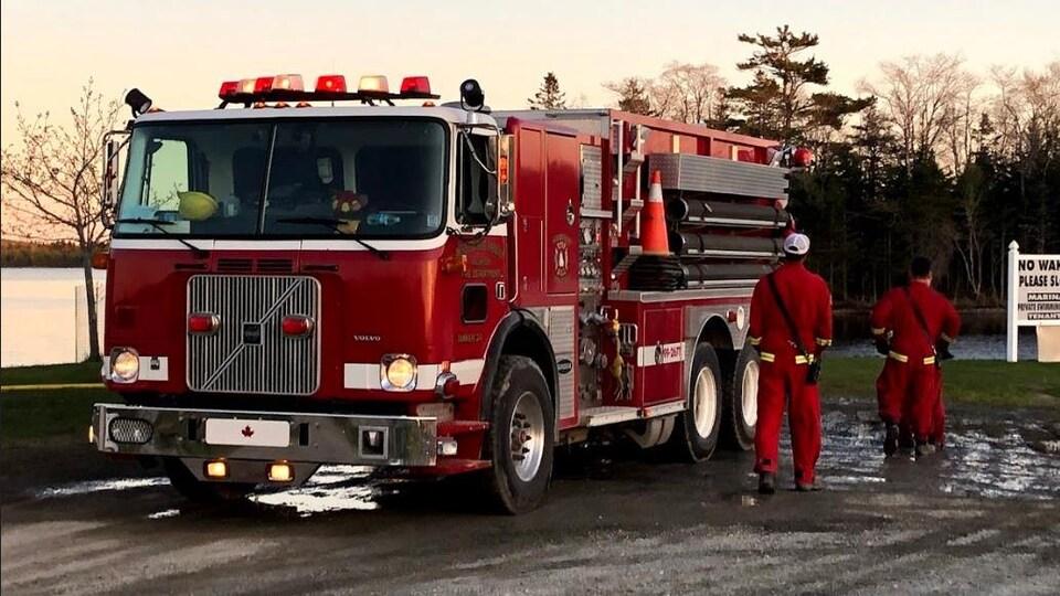 Deux pompiers et un camion de pompiers près d'un coucher de soleil.