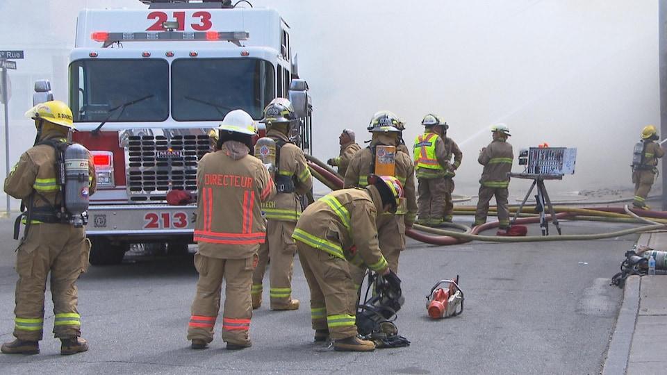 Des pompiers devant un camion de pompiers avec beaucoup de fumée