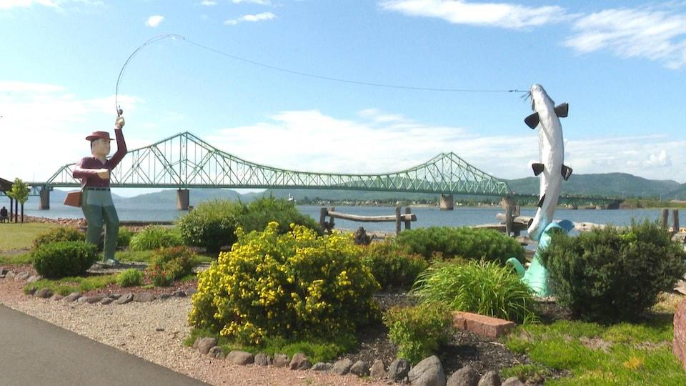 Des monuments qui représentent un pêcheur et un poisson, avec le pont en arrière.