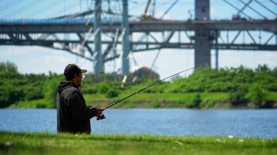 Un pêcheur sur le Saint-Laurent avec, en arrière-plan, les deux ponts Champlain.