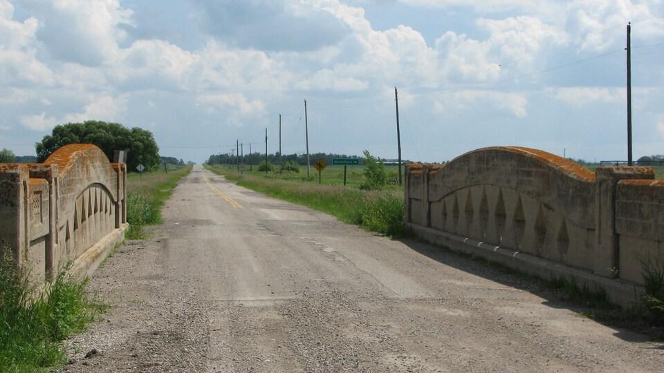 Un pont en ciment avec de la mousse orange sur une route de gravier.