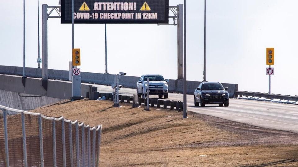 Des voitures sortent d'un point, et un panneau lumineux indique qu'un point de contrôle est en place plus loin en raison de la COVID-19.