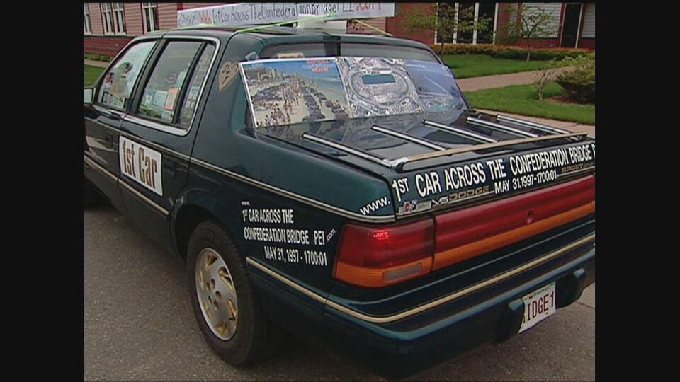 Une Dodge Spirit sur lequel est écrit « première voiture à avoir traversé le pont de la Confédération, le 31 mai 1997 »