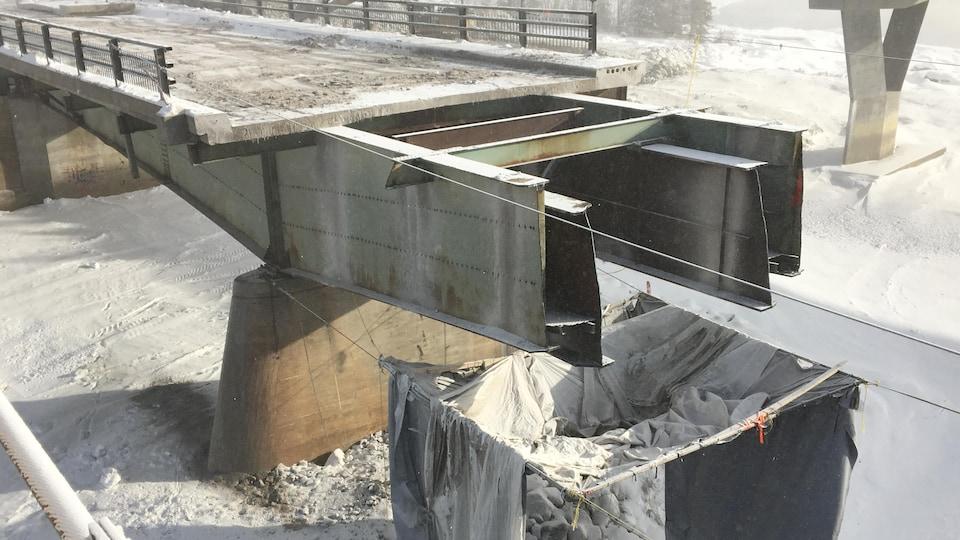 Une bâche est suspendue au-dessus de l'armature du pont.