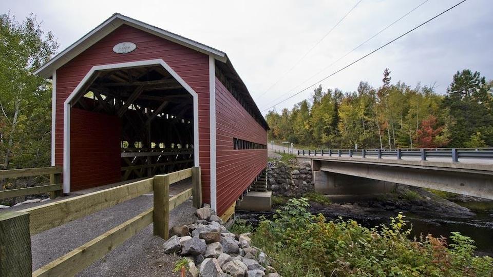 Ce pont couvert est construit en bois et peint en rouge.