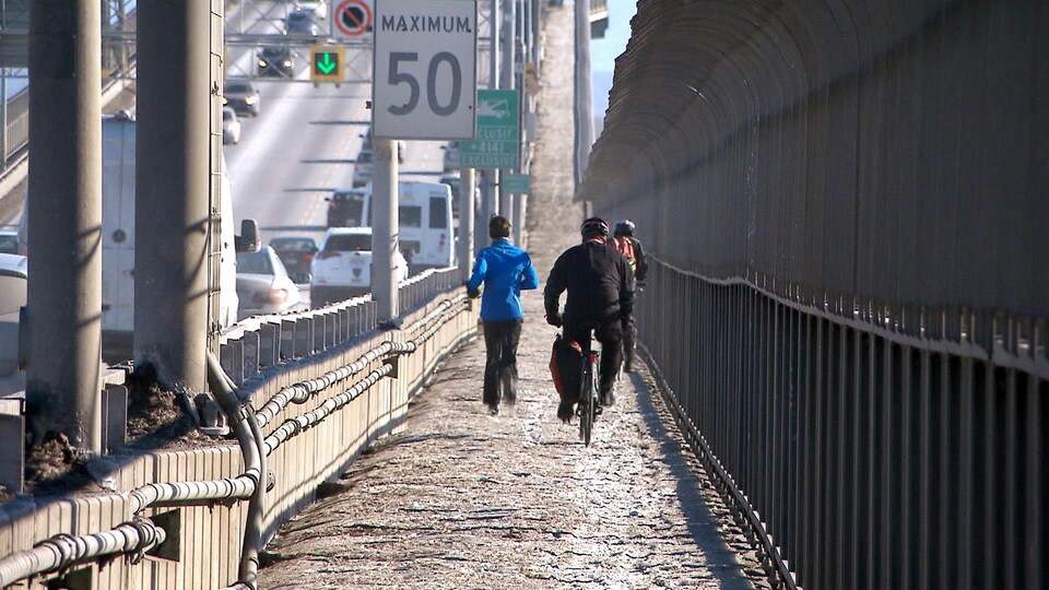 Des cyclistes et une joggeuse empruntent la piste mutlifonctionnelle, et ce, même s'il est n'est ni ouverte ni entretenue.