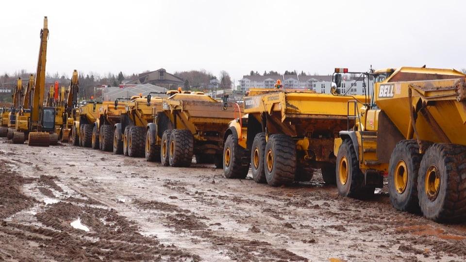 Plusieurs gros véhicules de construction dans la boue.