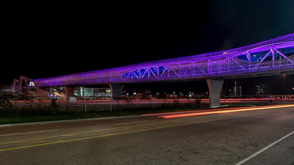 Un pont piétonnier couvert la nuit.